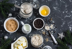 Christmas baking background. Flour, sugar, butter, rolled oats, eggs, chocolate chips on a dark background. Stock Photo