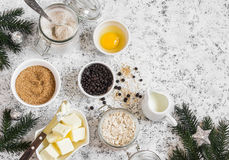 Christmas baking background. Flour, sugar, butter, rolled oats, eggs, chocolate chips on a light background. Stock Photos