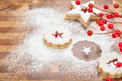 Christmas Baking. Christmas Linzer Cookies with powdered sugar on a wooden background royalty free stock photography