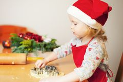 Christmas baking. Little girl at christmas bakery stock photos