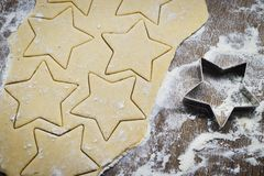 Christmas baking. Making gingerbread biscuits. Cookie dough and cookie cutters on kitchen counter. Christmas baking. Making gingerbread biscuits. Cookie dough stock photography