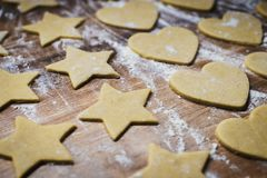 Christmas baking. Making gingerbread biscuits. Cookie dough on kitchen counter. Christmas baking. Making gingerbread biscuits. Cookie dough in heart and star stock images