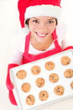 Christmas baking santa woman. Smiling happy having fun with Christmas preparations wearing Santa hat. Mixed race Chinese Asian and Caucasian female model making Stock Images