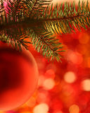 Christmas ball. On fir-tree against red blurred background royalty free stock photography