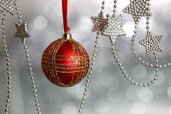 Christmas ball. Red Christmas ball on silver blurred background royalty free stock photography
