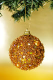 Christmas ball. A shiny golden christmas ball hanging on a christmas tree on a golden background Royalty Free Stock Photography