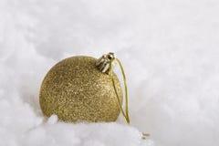 Christmas ball. Golden Christmas ball in snow Stock Photography