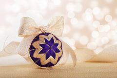 Christmas ball on abstract golden lights background Stock Photos