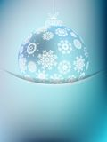 Christmas ball on abstract light. Background with snowflakes Stock Photos