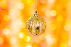 Christmas ball on a background of yellow and orange bokeh Stock Images