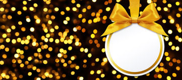 Christmas ball with bow hanging on lights background Royalty Free Stock Image