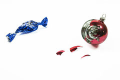 Christmas ball broken and blue candy wrapper Royalty Free Stock Photography