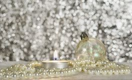 Christmas ball, candle and beads. Christmas ball, burning candle and beads on a silver background Stock Photos