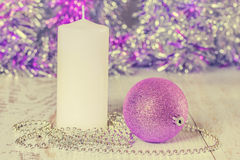 Christmas ball, candle and beads. Photo toned Royalty Free Stock Photos