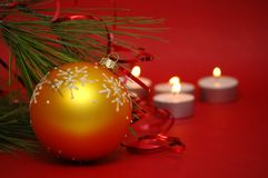 Christmas ball with candles. On a red background Royalty Free Stock Images