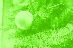 Christmas ball on the Christmas tree branch. green toned.  stock photo