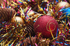 Christmas ball  and cones in multicolored tinsel Royalty Free Stock Image
