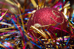 Christmas ball  and cones in multicolored tinsel Royalty Free Stock Photos
