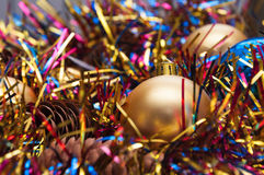 Christmas ball and cones in multicolored tinsel Stock Image