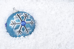 Christmas ball covered lying on snow. Blue Christmas ornament  with snow Stock Photography