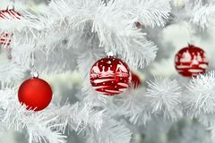 Red Christmas ball painted by hand in a white Christmas tree royalty free stock photos
