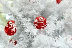 Red Christmas ball painted by hand in a white Christmas tree stock photo