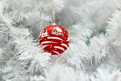 Red Christmas ball painted by hand in a white Christmas tree stock photos