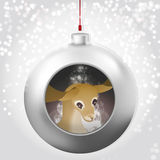 Christmas Ball with deer and magic glow inside on the snowy backdrop Stock Images