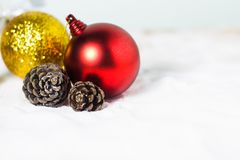 Christmas ball and dry pine cones on snow background Royalty Free Stock Photo