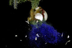 Christmas ball exploding. Glitters falling down. Royalty Free Stock Photo
