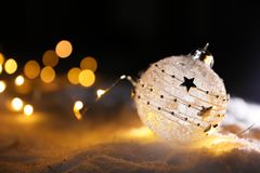 Christmas ball and fairy lights on white snow. Space for text royalty free stock photography