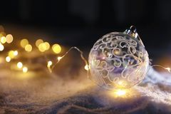 Christmas ball and fairy lights on white snow. Space for text stock photos