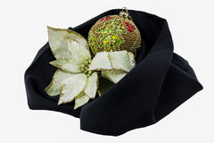 Christmas ball and flower cradled on a black cloth. Christmas decorative ball and flower resting and wrapped by a black cloth isolated on a white background Royalty Free Stock Images