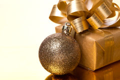 Christmas ball and gift box on a golden background Royalty Free Stock Photo