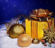 Christmas ball and gift box in snow. Christmas ball and gold gift box in snow Stock Image