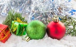 Christmas ball and gift box on the snow Stock Photos