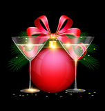 Christmas ball with glasses. Dark festive background with the large red ball and couple glasses of wine Stock Photo
