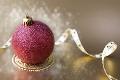 Christmas ball with gold ribbon bow with snow Royalty Free Stock Image