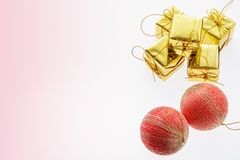 Christmas ball and golden gift box on light pink background. Royalty Free Stock Images