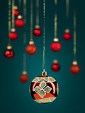 Christmas ball with golden glitter. Closeup of hanging christmas red globe with glittery decorations, with golden threads on blue gradient background with stock image