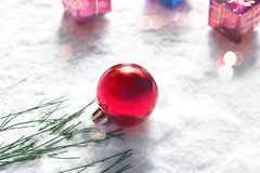 Christmas ball with green pine and gift box on snow background Stock Images