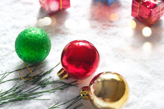 Christmas ball with green pine and gift box on snow morning background Royalty Free Stock Photos