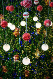 Christmas ball hanging on a Christmas tree with defocused lights. Royalty Free Stock Photo
