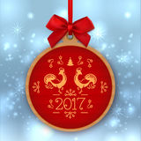 Christmas ball Happy New Year 2017, Greeting card template, label. Christmas ball Happy New Year 2017, Round label with red bow,  on winter background. Golden Royalty Free Stock Photos