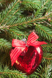 Christmas ball (heart) on fir branch background Royalty Free Stock Photos