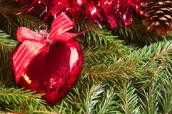 Christmas ball (heart) on the tinsel background Royalty Free Stock Images