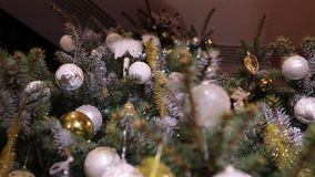 Christmas ball, christmas lights hanging in a tree, New Year, silver bauble hanging from a decorated Christmas tree. Movement, shallow depth of field, view