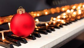 Christmas ball and lights on a piano keyboard. Christmas ball and lights on a classical piano keyboard royalty free stock image