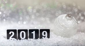 Christmas ball and new year 2019, on snow, abstract bokeh lights background. Copy space stock photography