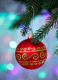 Christmas ball with ornament hanging on xmas tree, defocused lights Stock Image